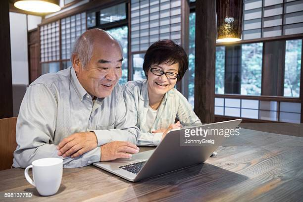 Japanese couple using laptop at home