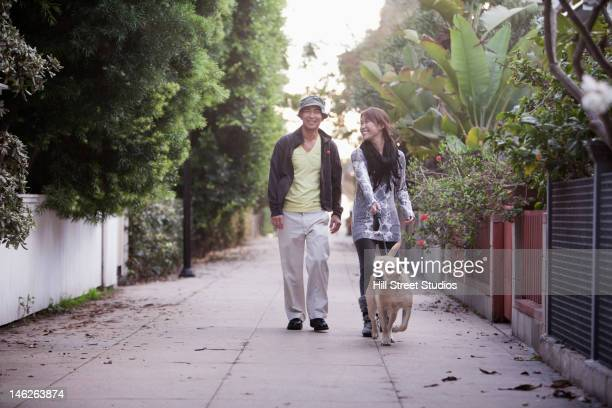 Japanese couple walking dog in alley