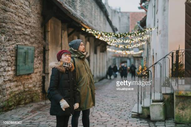 japanese couple walking in old town during christmas - estonia stock pictures, royalty-free photos & images