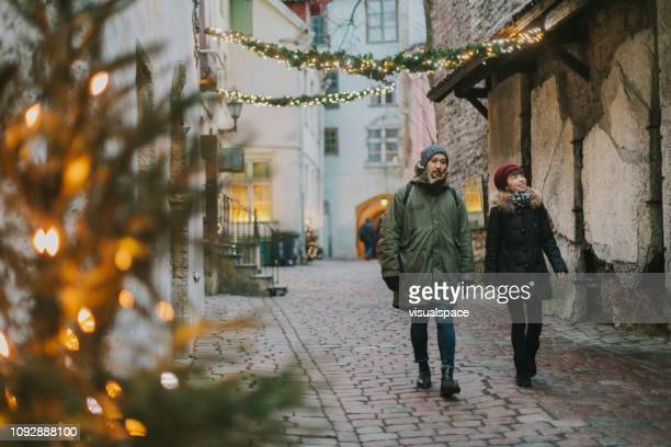 japanese couple walking in tallinn old town during christmas - tallinn stock pictures, royalty-free photos & images