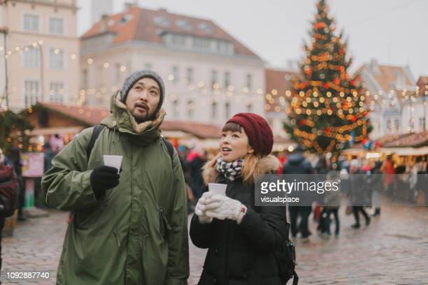 Japanese couple walks at Christmas market and drinks mulled wine