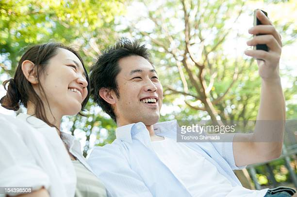 A Japanese couple watcing a smartphone