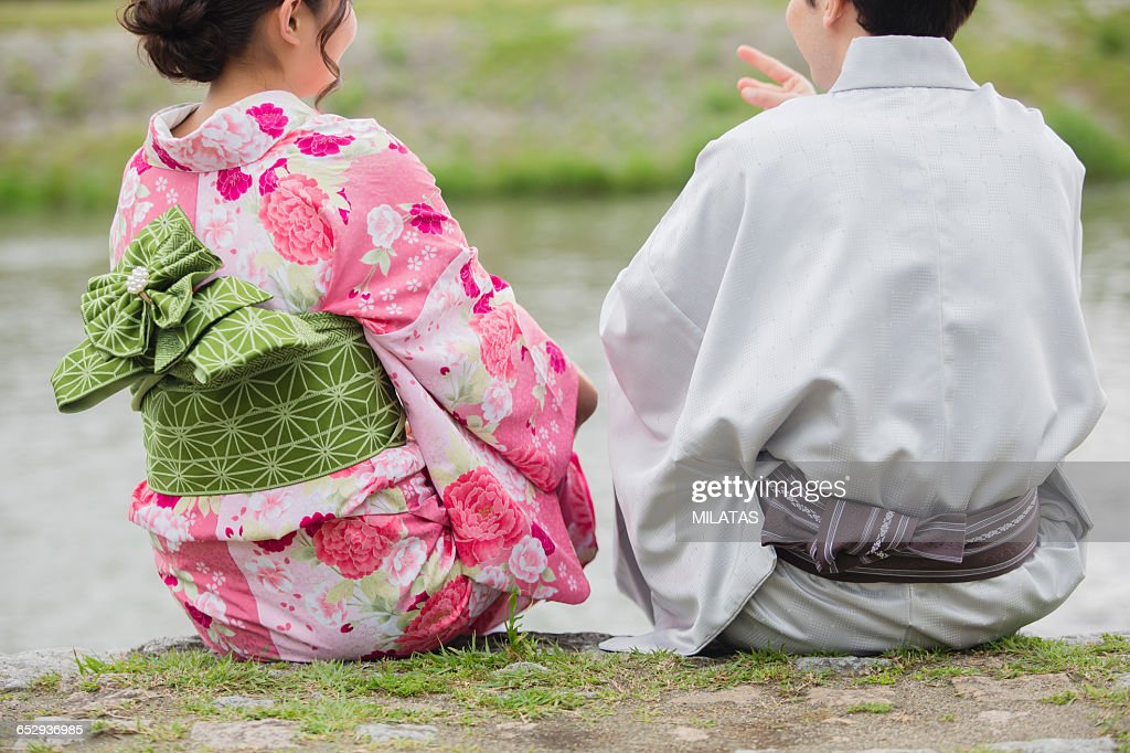 Japanese couples sit in river beach : Stock Photo