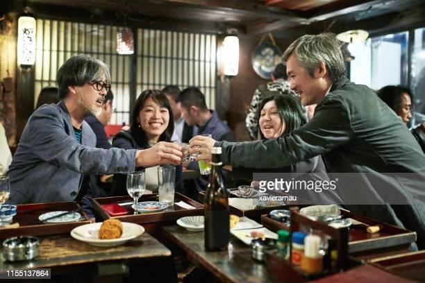 日本のカップルが東京寿司バーとレストランで乾杯 - 乾杯 ストックフォトと画像