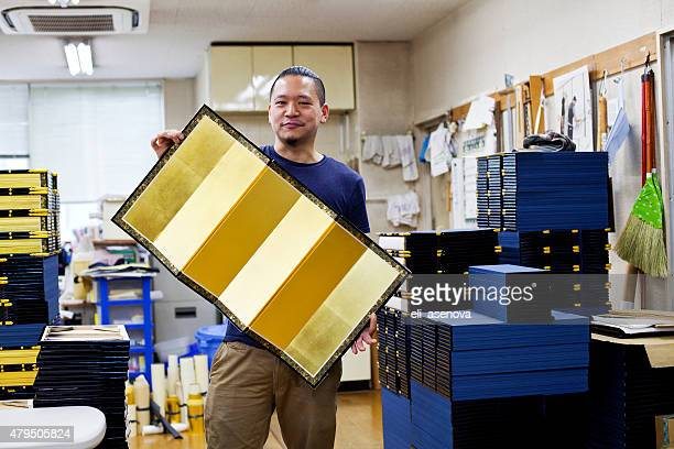 Japanese craftsman is holding a picture frame, Tokyo.