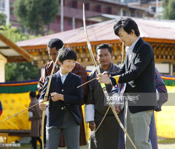 Japanese Crown Prince Fumihito and his 12yearold son Prince Hisahito try Bhutanese traditional archery at the national court in the country's capital...