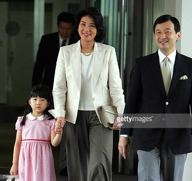 Japanese Crown Prince Naruhito and Princess Masako accompanied by their daughter Princess Aiko walk to their plane at the new Tokyo International...