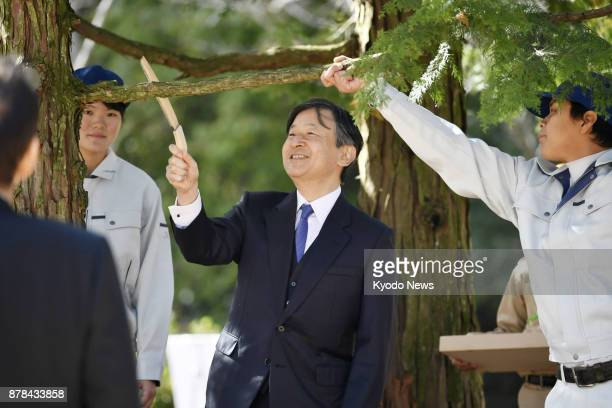 Japanese Crown Prince Naruhito takes cuts a hinoki cypress tree branch at a national tree planting ceremony in Manno Kagawa Prefecture western Japan...