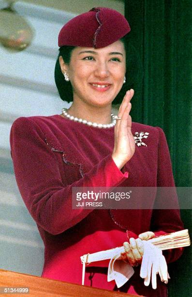 Japanese Crown Princess Masako smiles as she waves to wellwishers from behind bulletproof glass on a balcony to celebrate the 66th birthday of...