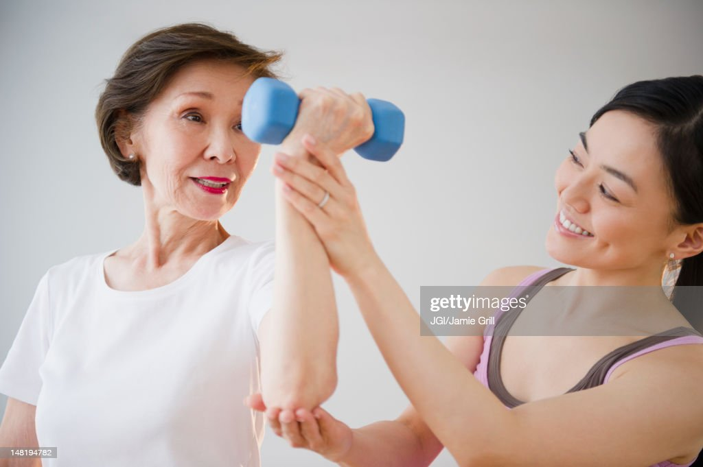 Japanese daughter helping mother with exercise : Stock Photo