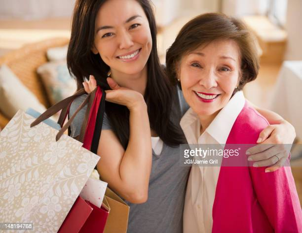 Japanese daughter holding shopping bags and hugging mother