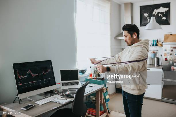 japanese day trader talking with clients on conference call - stretching stock pictures, royalty-free photos & images
