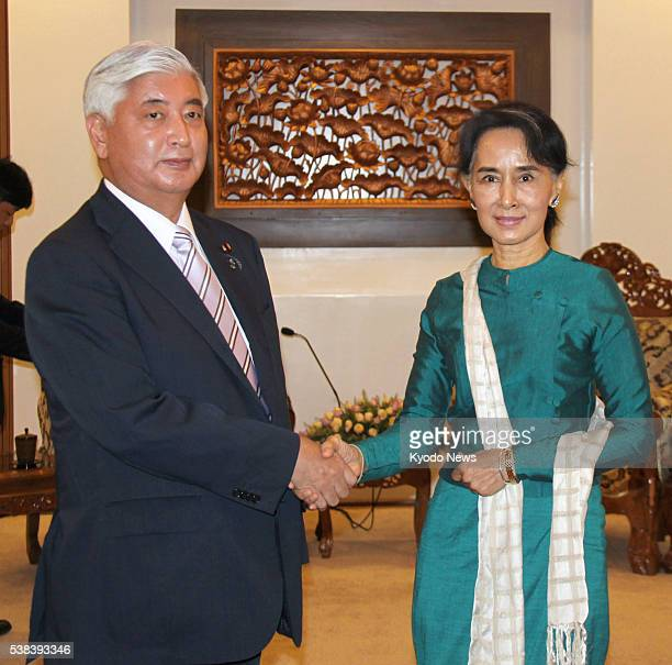 Japanese Defense Minister Gen Nakatani and Myanmar's de facto leader State Counselor Aung San Suu Kyi shake hands before talks in Naypyitaw on June 6...