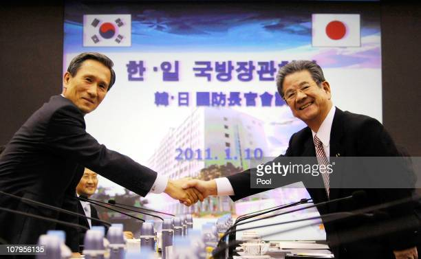 Japanese Defense Minister Toshimi Kitazawa shakes hands with South Korean Defense Minister Kim KwanJin during their meting at Defence Ministry on...
