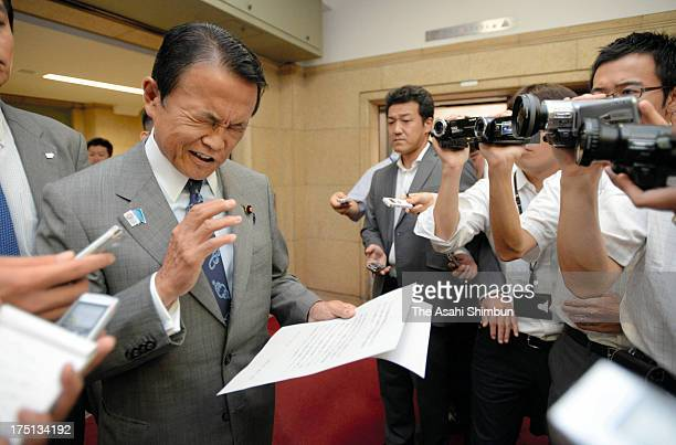 Japanese Deputy Prime Minister and Finance Minister Taro Aso reads a comment to retract his recent remarks at Finance Ministry on August 1 2013 in...