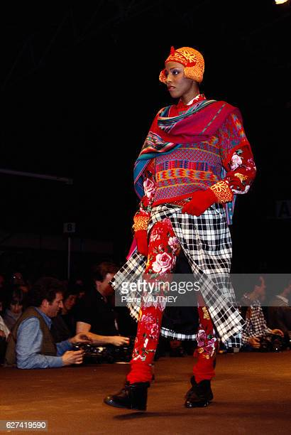 Japanese design house Kenzo shows its 1984-1985 fall-winter women's ready-to-wear line in Paris. The model is wearing a plaid skirt over floral pants...
