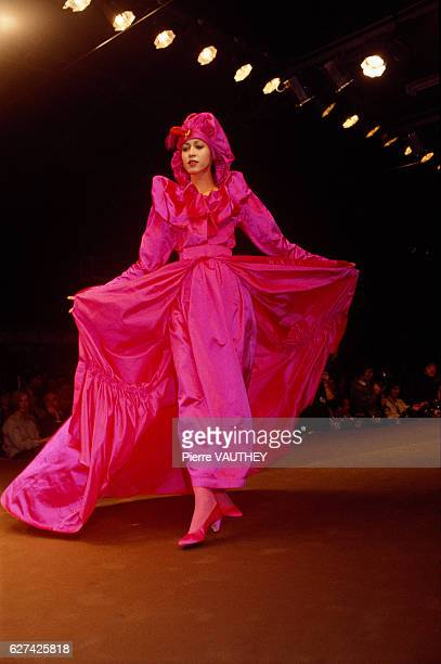 Japanese design house Kenzo shows its 1984-1985 fall-winter women's ready-to-wear line in Paris. The model is wearing a bright fuchsia dress with a...