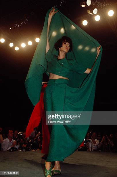 Japanese design house Kenzo shows its 1986 spring-summer women's ready-to-wear line in Paris. The model is wearing a green dress with a long train.