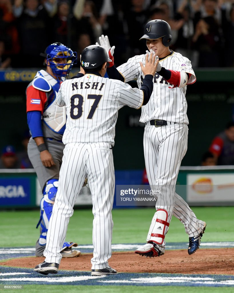 Japanese designated hitter Tetsuto Yamada (R) arrives at the home plate as he celebrates with coach Toshihisa Nishi (C) beside Cuban catcher Yosvani Alarcon (L) after hitting a two-run homer in bottom of the eighth inning during the World Baseball Classic Pool E second round match between Cuba and Japan at Tokyo Dome in Tokyo on March 14, 2017. /