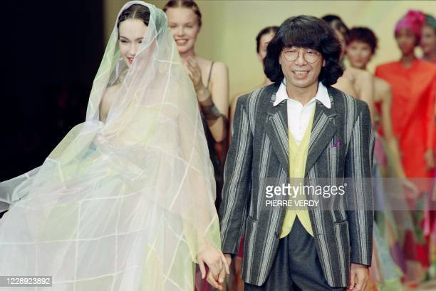 Japanese designer Kenzo greets with a model wearing the wedding dress at the end of the Spring-Summer 1994 ready-to-wear collection show, on October...