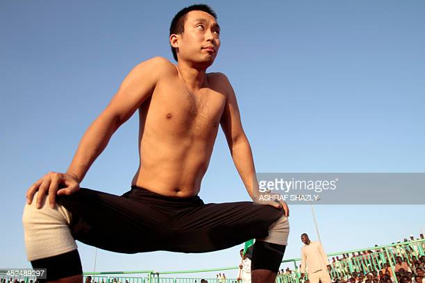 Japanese diplomat Yasuhiro Murotatsu aka Muro arrives to compete in a traditional Nuba wrestling match on November 29 2013 at a stadium in a district...