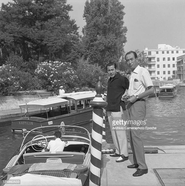 Japanese director Akira Kurosawa portrayed with the japanese actor Toshiro Mifune while waiting to go on board of a water taxi berthed nearby Venice...