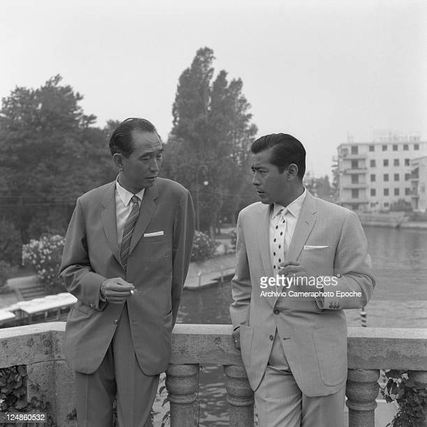 Japanese director Akira Kurosawa wearing a suit and a striped tie portrayed while smoking a cigarette with the japanese actor Toshiro Mifune wearing...