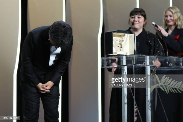 Japanese director Hirokazu KoreEda acknowledges applause on stage as a translator and Australian actress and President of the Jury Cate Blanchett...