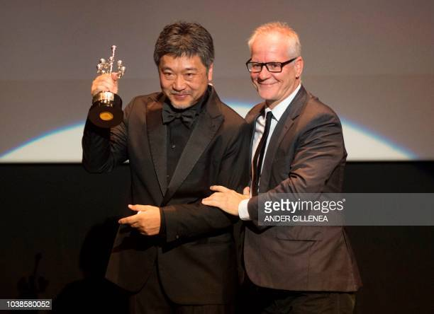 Japanese director Hirokazu KoreEda holds up the Donostia Award in recognition of his prestigious film career beside the General Delegate of the...