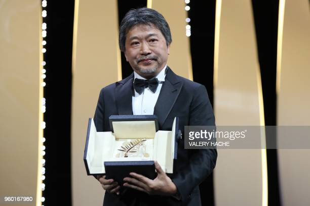 TOPSHOT Japanese director Hirokazu KoreEda poses on stage after he was awarded with the Palme d'Or for the film Shoplifters on May 19 2018 during the...