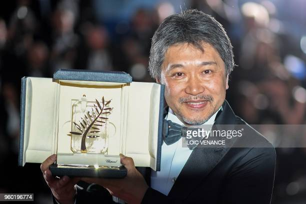 TOPSHOT Japanese director Hirokazu KoreEda poses with his trophy on May 19 2018 during a photocall after he won the Palme d'Or for the film...
