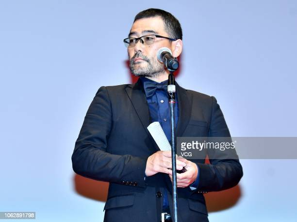 Japanese director Masaharu Take poses with trophy during the closing ceremony of the 31st Tokyo International Film Festival on November 2 2018 in...
