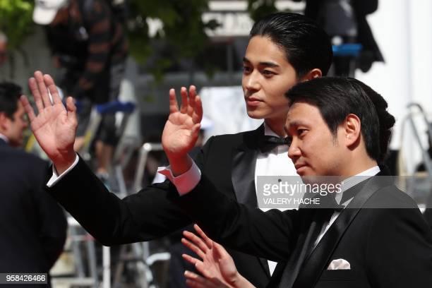 Japanese director Ryusuke Hamaguchi and Japanese actor Masahiro Higashide wave as they arrive on May 14 2018 for the screening of the film Asako I II...