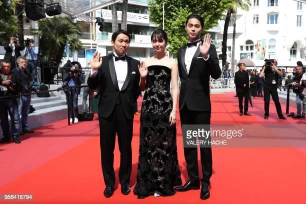 Japanese director Ryusuke Hamaguchi Japanese actress Erika Karata and Japanese actor Masahiro Higashide wave as they arrive on May 14 2018 for the...
