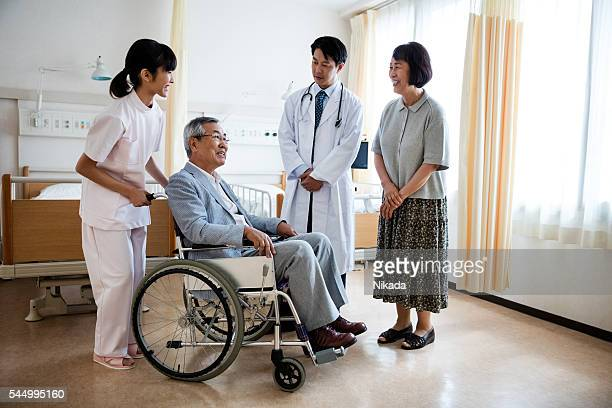 Japanese doctor attending to a patient in wheelchair