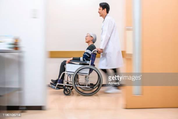 日本人医師が車椅子で患者を廊下に押し倒す - 公共の建物 ストックフォトと画像