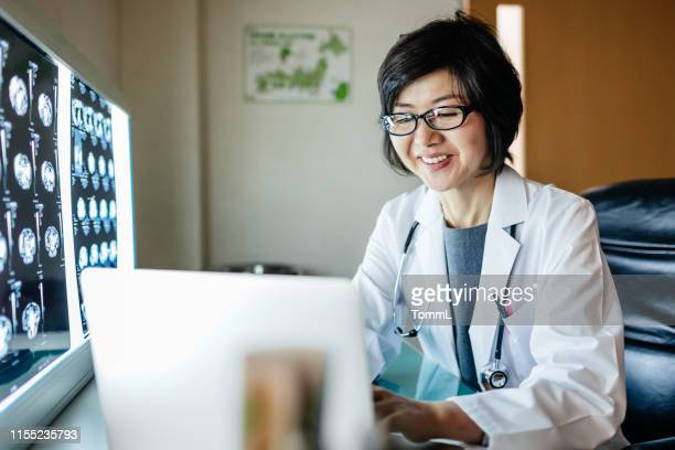 japanese doctor using computer and looking at x-rays - medical x ray stock pictures, royalty-free photos & images