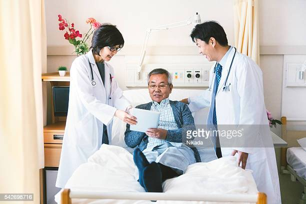 Japanese doctors talking to a patient in a hospital
