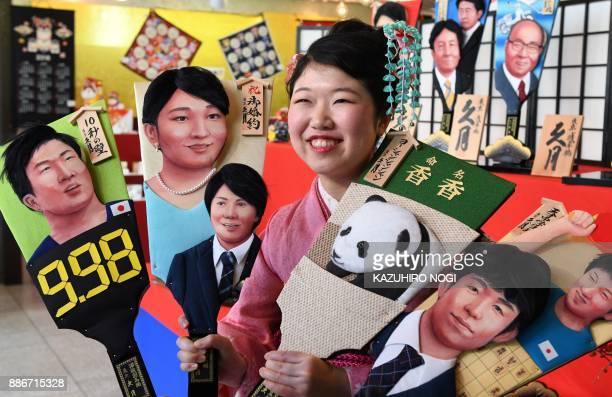 Japanese doll maker Kyugetsu employee Haruka Sasakura wearing a kimono dress displays wooden battledores or 'hagoita' decorated with images of the...