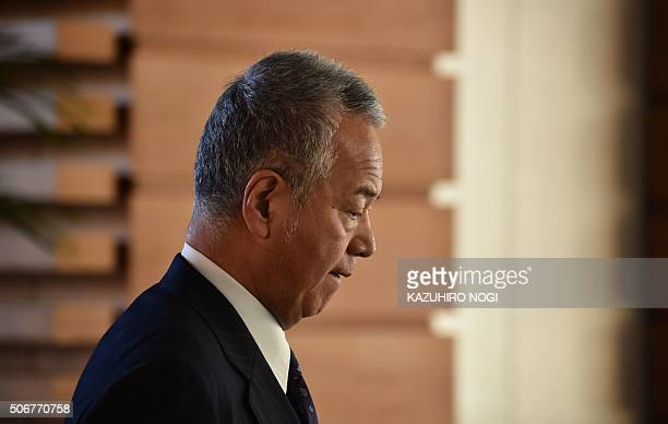 Japanese Economic and Fiscal Policy Minister Akira Amari arrives at the prime minister's official residence to attend a cabinet meeting in Tokyo on...