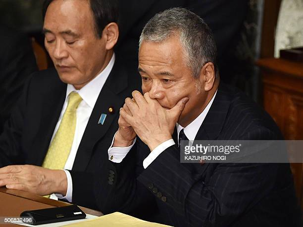 Japanese Economy and Fiscal Policy Minister Akira Amari listens to questions by the main opposition Democratic Party of Japan during a plenary...