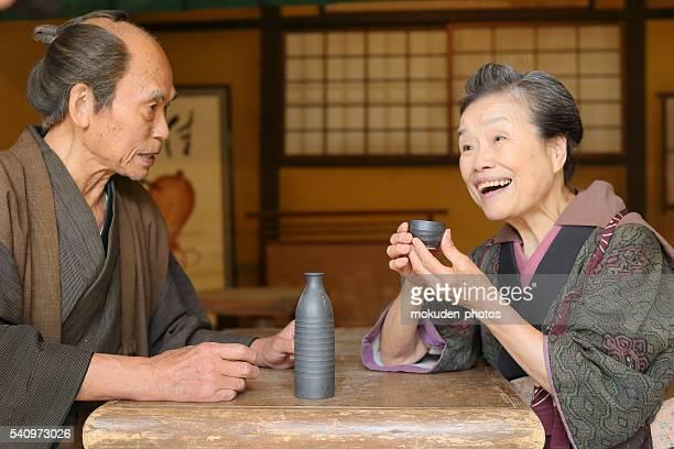 pareja de ancianos japonés para disfrutar de una bebida junto un - saki fotografías e imágenes de stock