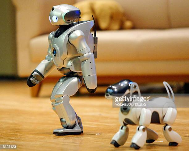 Japanese electronics giant Sony's humanoid robot Qrio and pet robot Aibo walk together as Sony Fujitsu and Mitsubishi Heavy Industry demonstrate the...