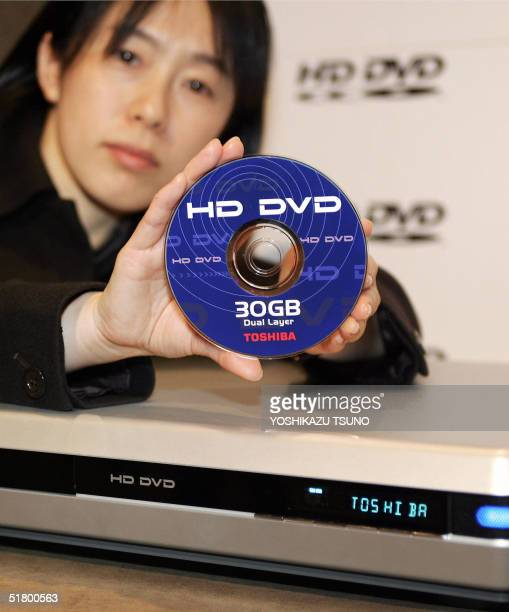 Japanese electronics giant Toshiba employee Junko Furuta displays the prototype model of the next generation DVD HD DVD player and its 30GB disc at a...