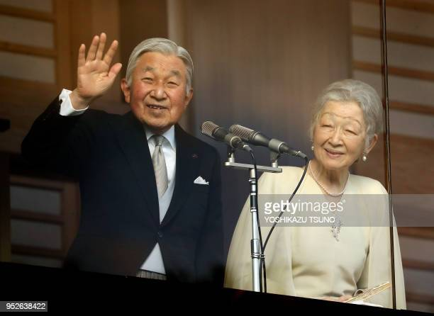 Japanese Emperor Akihito accompanied by Empress Michiko waves to wellwishers gathered for the annual New Year's greetings at the Imperial Palace in...