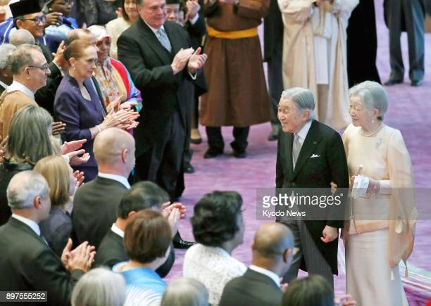 Japanese Emperor Akihito accompanied by his wife Empress Michiko is applauded by ambassadors to Japan during an event at the Imperial Palace in Tokyo...