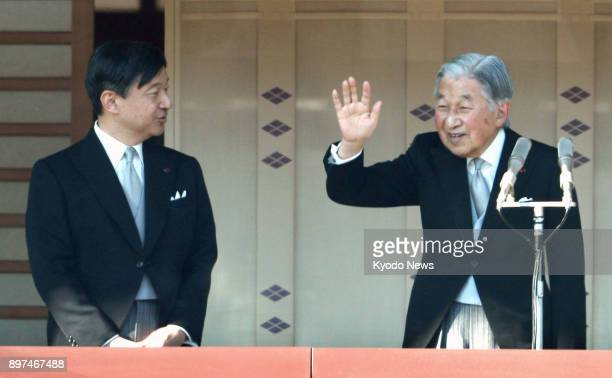 Japanese Emperor Akihito alongside Crown Prince Naruhito waves to the crowd gathered at the Imperial Palace in Tokyo to celebrate his 84th birthday...
