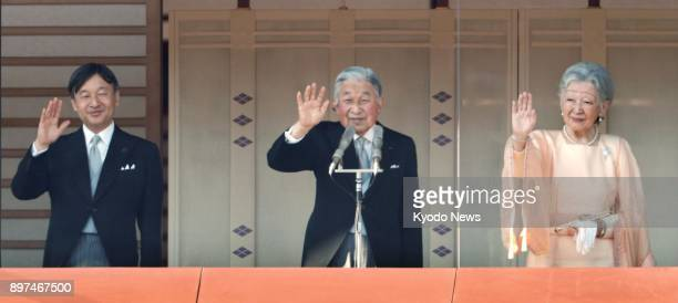 Japanese Emperor Akihito alongside Empress Michiko and Crown Prince Naruhito waves to the crowd gathered at the Imperial Palace in Tokyo to celebrate...