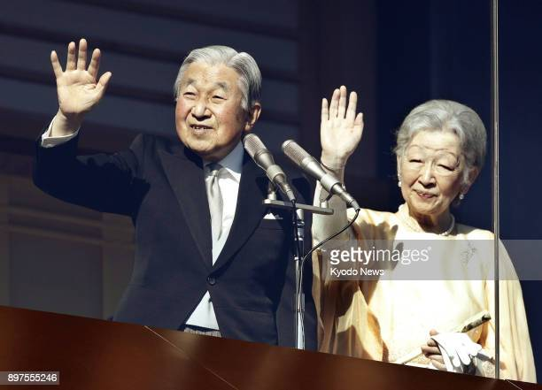 Japanese Emperor Akihito alongside his wife Empress Michiko waves to the crowd gathered at the Imperial Palace in Tokyo to celebrate his 84th...