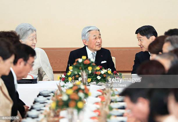Japanese Emperor Akihito and Crown Prince Naruhito chat alongside Empress Michiko during a banquet at the Imperial Palace in Tokyo to celebrate the...